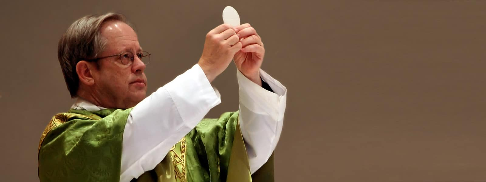 Priest elevates the Eucharist during Mass. Receiving the Eucharist is one precept of the Catholic Church.