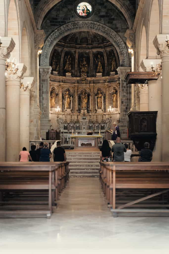 people sitting on brown wooden bench inside cathedral