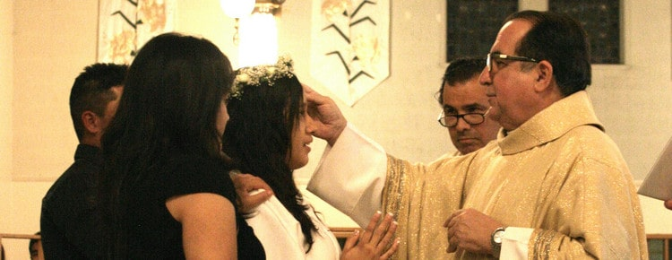 Young woman is confirmed by priest